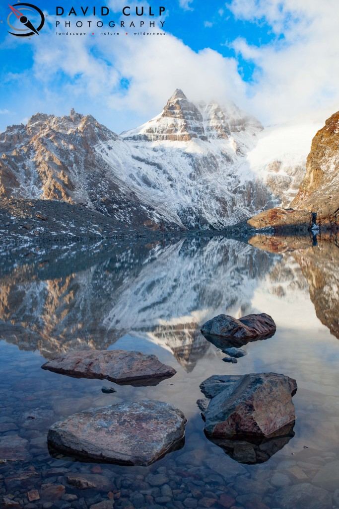 The sun lights up the nearby peaks at dawn creating a stunning reflection in a glacial catch lake.